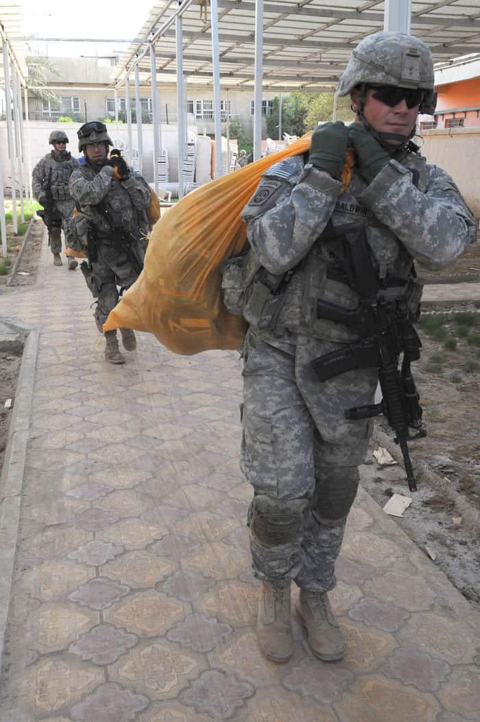 Paratroopers assigned to Headquarters and Headquarters Troop, 5th Squadron, 73rd Cavalry Regiment, carry bags of soccer equipment and other goods to Rusafa council headquarters building in a humanitarian mission.