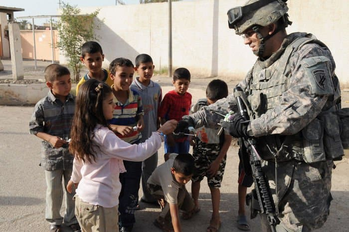 Sgt. Bryan Patenge, of Phoenix, Ariz., hands out candy to children during a humanitarian mission in the Idrissi neighborhood.
