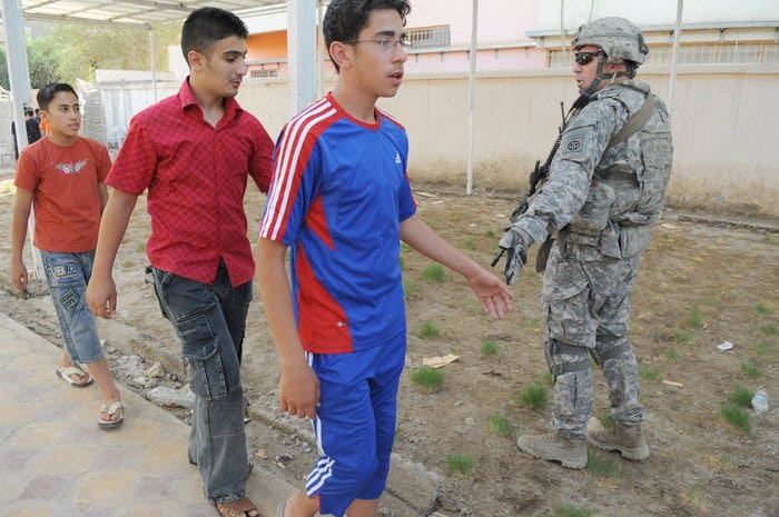 Sgt. 1st Class Daniel Workman, of Jacksonville, Fla., a platoon sergeant, greets Iraqi children during a humanitarian mission in the Rusafa district of eastern Baghdad.