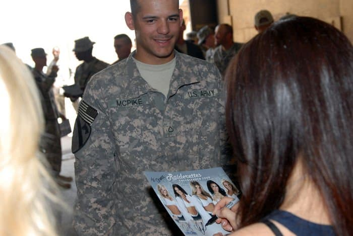 Pfc. Chance McPike, of Troy, Mo., a 1st Cavalry generator mechanic, waits for autographs from the Oakland Raiderettes.