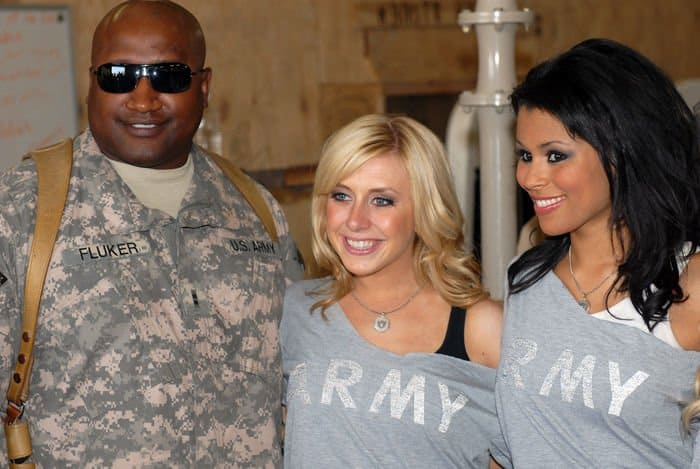 Chief Warrant Officer 2 Robert Fluker Jr., battalion maintenance technician assigned to Division Special Troops Battalion, 1st Cavalry Division, poses with Oakland Raiderettes, at the DSTB motor pool.