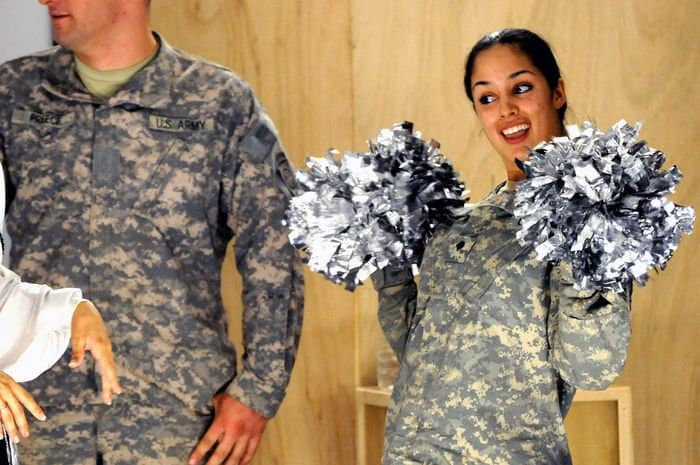Spc. Ikram Mansori, of San Francisco, Calif., does her best cheerleader impression during the Raiderettes show at Joint Security Station Loyalty.