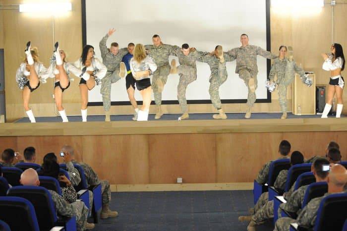 82nd Airborne Division Paratroopers dance with cheerleaders from the NFL Oakland Raiders.