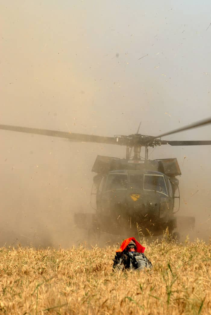 A Soldier of B Troop, 2nd Battalion, 8th Cavalry Regiment, 2BCT, 1ID, stands in a wheat field amid the rotor wash and flying debris to mark the spot for the UH 60 Blackhawk helicopter to land. It will take the injured Soldiers to a hospital for further medical examination.