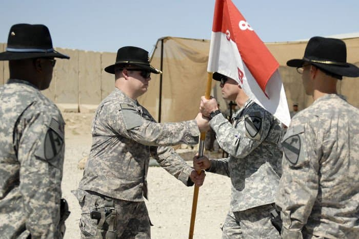 Cpt. Jeffrey Hendrix, outgoing commander for B. Co. 3rd Bn., 8th Cav. Regt., relinquishes command by passing the company guidon to Lt. Col. Phil Brooks, battalion commander of 3rd Bn., 8th Cav. Regt.