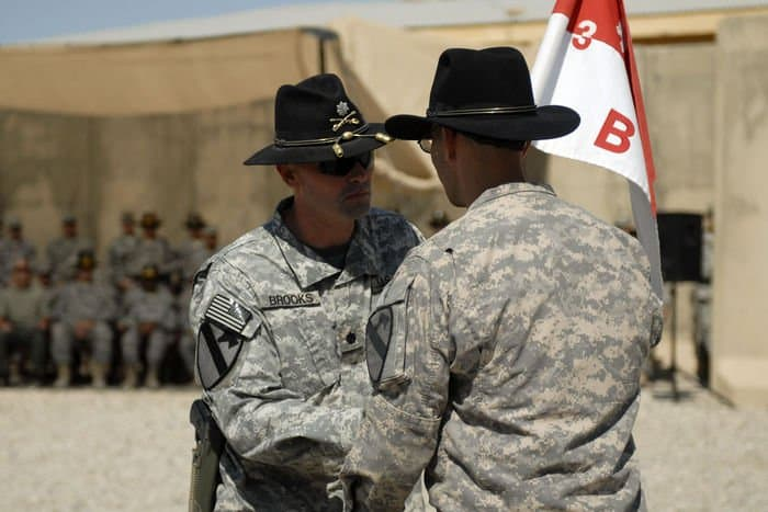 Lt. Col. Phil Brooks, battalion commander of 3rd Bn., 8th Cav. Regt., passes the B. Co. guidon to Cpt. Shane Aguero, the incoming commander of B. Co.