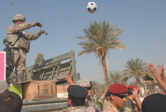 A U.S. Paratrooper, 505th Parachute Infantry Regiment, throws a soccer ball to a group of Iraqi children during a combined humanitarian mission.