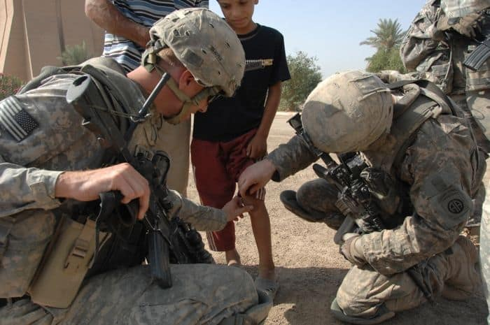 U.S. Paratrooper medics assist Iraqi medical personnel during a free medical screening for local residents in the town of Salman Pak, Iraq.