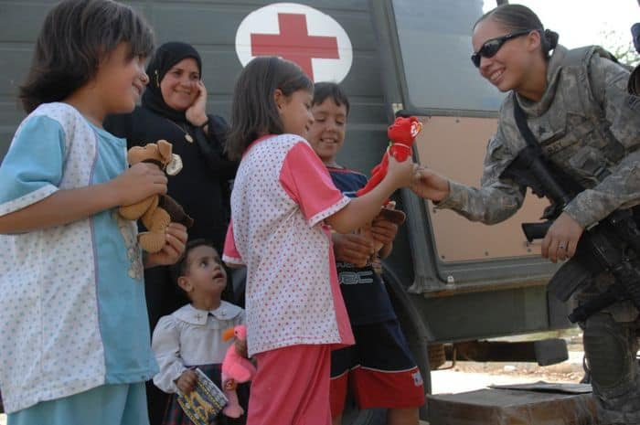 Sgt. Kristina Ray, of Enterprise, Alaska, a medic, hands a stuffed animal to an Iraqi girl.