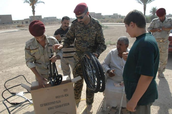 Iraqi Army Soldiers help assemble a wheelchair, in the town of Salman Pak, Iraq.