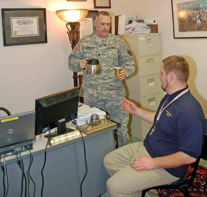 Lt. Col. Edward McDonald, a legal assistance attorney with the Judge Advocate General office at Camp Atterbury, pours Rocky Stroup a cup of coffee.