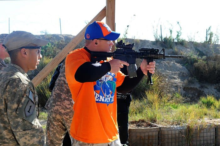 World Wrestling Entertainment superstar, John Cena, tests his skills at firing an M 4 carbine assault rifle during a visit to FOB Paliwoda.