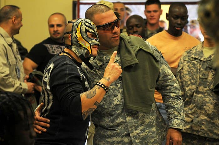 Sergeant 1st Class Juan F. Cruz, a career counselor with Headquarters and Headquarters Company, 4th Infantry BCT, 4th Infantry BCT, 1ID out of Fort Riley, Kan., poses for a picture with World Wrestling Entertainment superstar, Ray Mysterio.