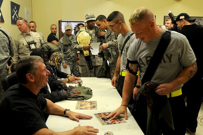 Soldiers of the 1st Battalion, 28th Infantry Regiment, 4th Infantry BCT, 1ID out of Fort Riley, Kan., file through the unit conference room at FOB Paliwoda, to meet and receive autographs from the six superstars of the World Wrestling Entertainment, including WWE Chairman of the Board and Chief Executive Officer, Vince McMahon.