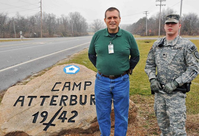 Civilian Contractor Mark Trowbridge stands with Military Police Officer Spc. Stephen Strebinger in front of the Camp Atterbury rock in central Indiana roughly four months after Strebinger assisted in saving Trowbridge.
