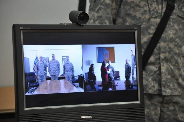 A Task Force 38 video teleconference screen shows both views from Katterbach, Germany and Joint Base Balad, Iraq during a promotion ceremony for Staff Sgt. James Pedersen.