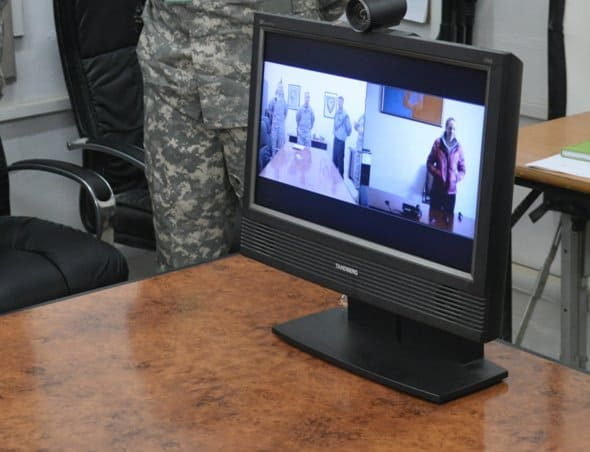 A Task Force 38 video teleconference screen shows both views from Katterbach, Germany and Joint Base Balad, Iraq, after instructor pilot Ryan Mahany was promoted to chief warrant officer 3.