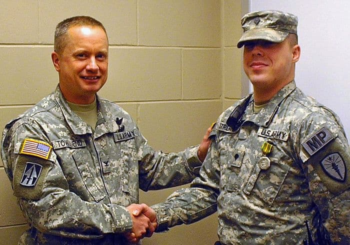 Camp Atterbury Commander Col. Todd Townsend shakes the hand of Military Police Officer Spc. Stephen Strebinger for his quick actions which led to the success in a team effort to save the life of a civilian contractor at Camp Atterbury