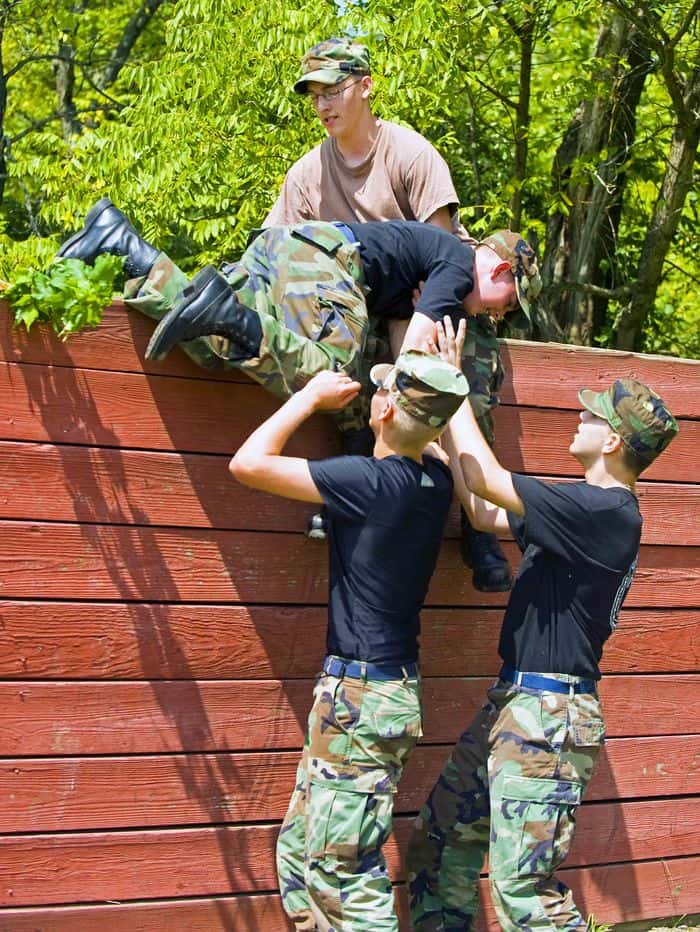 Civil Air Patrol Cadets work together to overcome a wall at the conditioning course at Camp Atterbury Joint Maneuver Training Center in central Indiana, part of their annual encampment training.