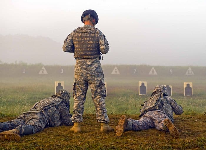 A Soldier of the Camp Atterbury Range Training Team watches as an Airman to his left and a Soldier to his right engage targets on the Stress Fire range at Camp Atterbury.