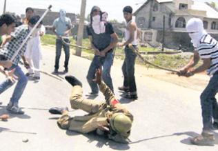 a securityman is being beaten by kashmiri youths