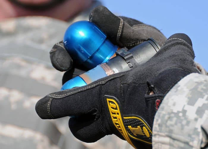 An Indiana National Guard Soldier inspects a 40mm grenade before loading the ammunition into the Mk 19 grenade launcher.