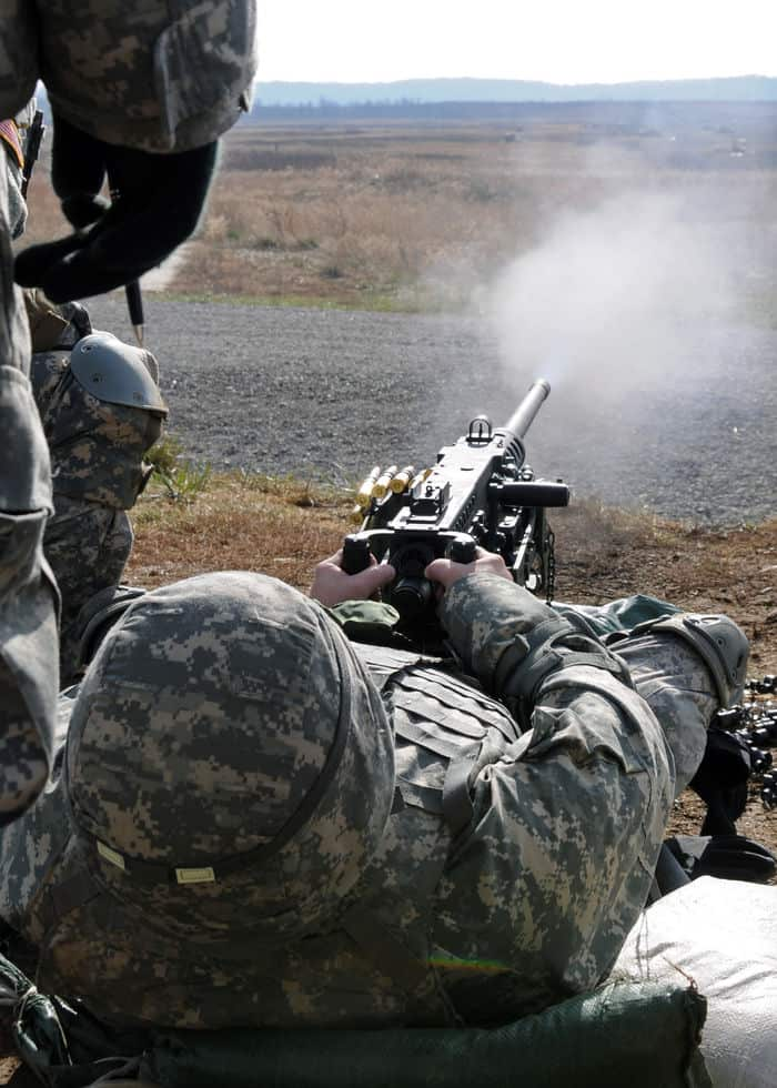 Sgt. Steven Shaw, an Indiana National Guard Soldier leans back to get lineof sight as he fires a .50 caliber machine gun during weapon qualification training