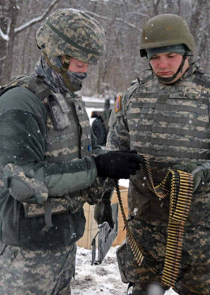 Sgt. Drue Gilbert and Pvt. Jess Neal inspect their ammunition for a Squad Automatic Weapon.
