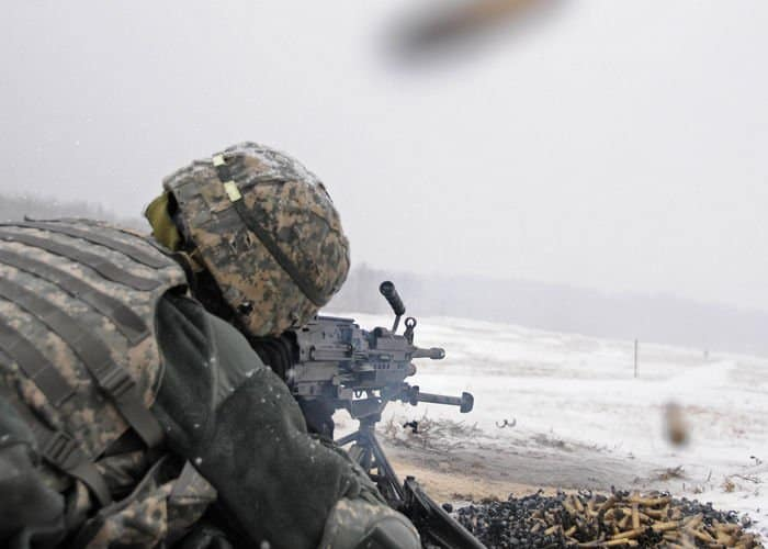 Sgt. Drue Gilbert, a signal support systems specialist, fires a Squad Automatic Weapon.