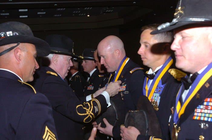 Retired Lt. Col. Bruce Crandall, Medal of Honor recipient, inducts Chief Warrant Officer 3 Bill McKenna into the Order of St. Michael during the 1st Squadron, 6th Cavalry Regiment, ball.