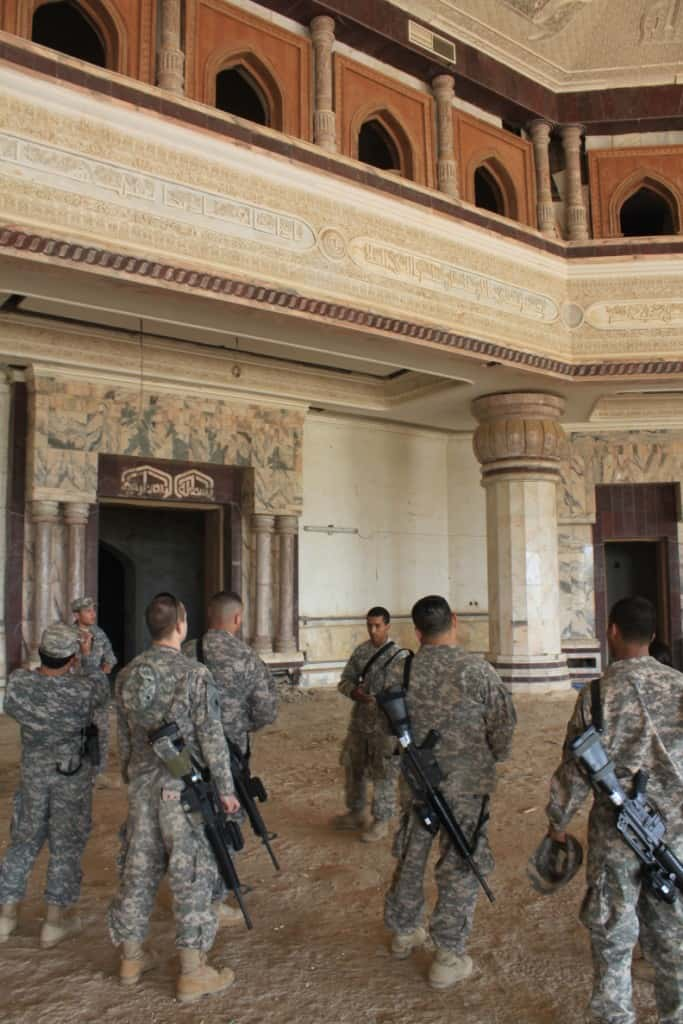 Soldiers from the 40th Combat Aviation Brigade take a tour of Saddam Hussein Victory Over America palace, bombed in the beginning of Operation Iraqi Freedom.