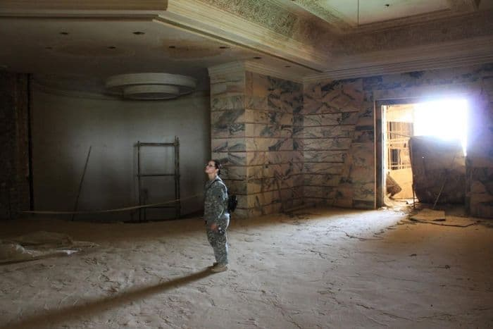 Pvt. Claudia Marquez stands in a room inside Saddam Hussein Victory Over America palace while on a tour of historic sites on Victory Base Complex, Iraq.