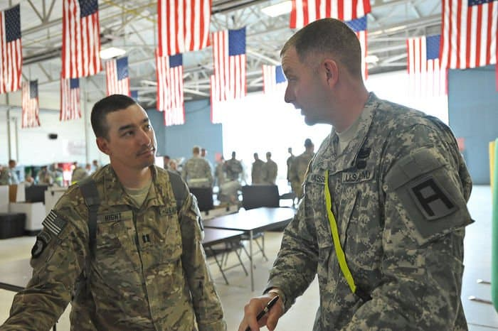 Staff Sgt. Thomas Massey, right, a unit movement assister with Division West 191st Infantry Brigade, talks with Capt. Dale Hight, at Volk Field, Wis.