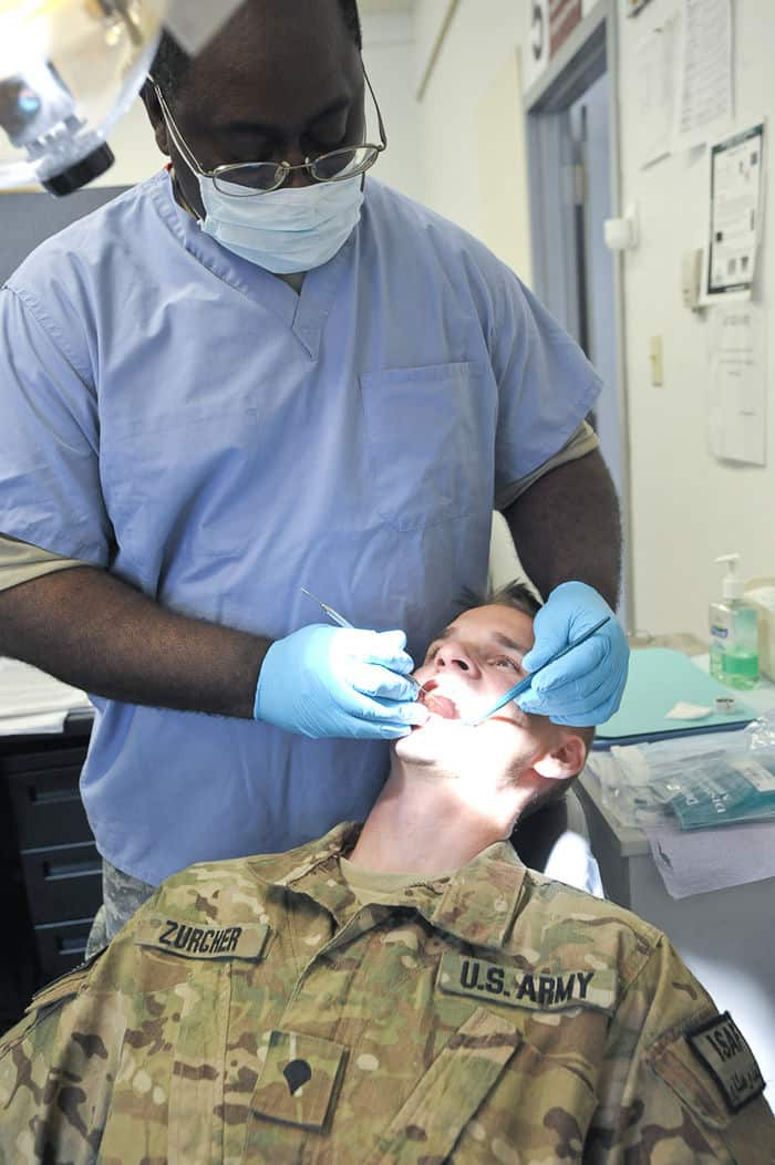 Spc. Lucas Zurcher of the Iowa Army National Guard 2BCT, 34ID, has his teeth examined by Maj. Aaron Ohemeng.