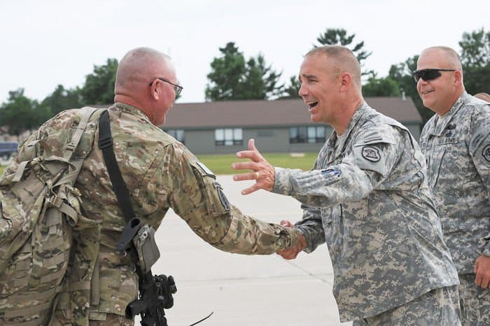 Adjutant General of Iowa Maj. Gen. Timothy Orr, second from right, and Command Sgt. Maj. John Breitsprecker, right, Iowa Army National Guard command sergeant major, welcome back Soldiers of the Iowa Army National Guard 2BCT, 34ID.