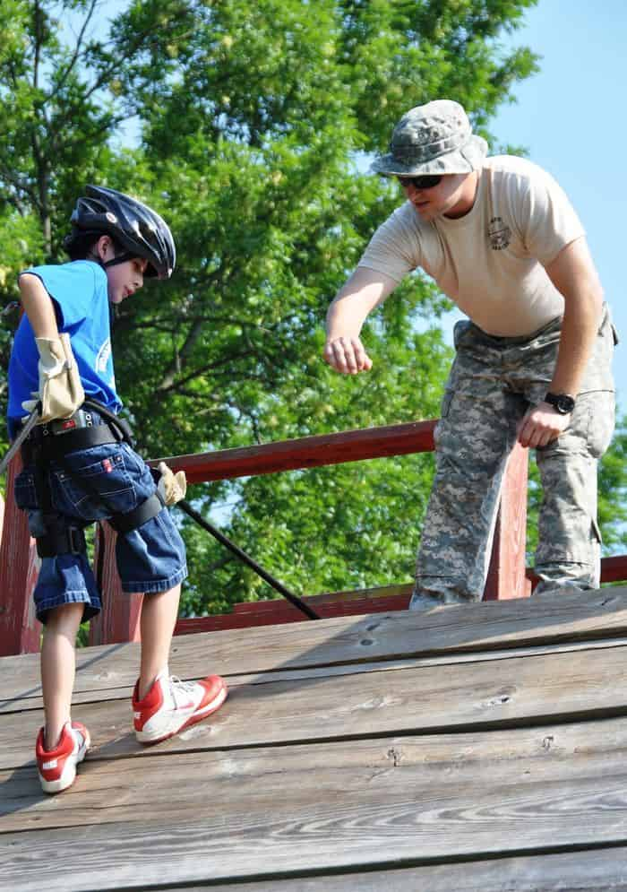 Travis Cooper, of Indianapolis, prepares to rappel down a short tower with the help of Sgt. Alexander Zartman, during Kids Annual Training at Camp Atterbury Joint Maneuver Training Center.