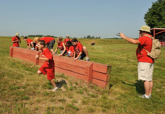 Children attending the Indiana National Guard Kids Annual Training summer camp vault over a low wall during a race through an obstacle course at Camp Atterbury.