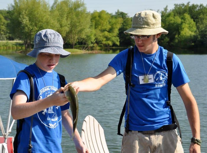 Cyrus Nida, and Kids AT Junior Counselor Christian Ruczynski, look over a fish caught at the Major General Carl G. Farrell Recreation Area on Camp Atterbury Joint Maneuver Training Center, Ind.