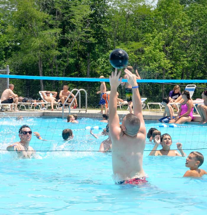Campers and counselors at Kids AT enjoy a game of volleyball in the swimming pool during a break from activities at Camp Atterbury Joint Maneuver Joint Maneuver Training Center.