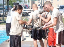 Cadets wring out their ACU pants after learning to use their uniform to make a floatation device, completing a day of water survival training at the Camp Atterbury pool.