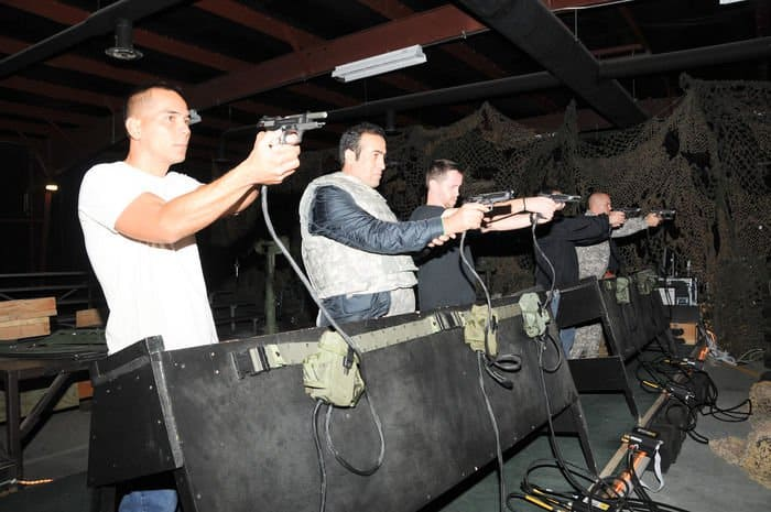 Civilians going through mobilization training at Camp Atterbury Joint Maneuver Training Center get weapons familiarization training in a firearms simulator.