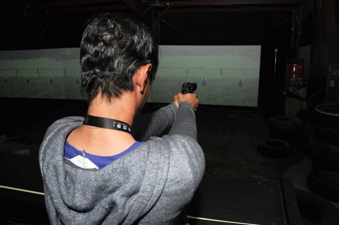 Kimberly Victorian, a Lafayette, La. native and intelligence analyst for SOS International, Ltd., fires an M9 pistol at simulated targets in weapons training.