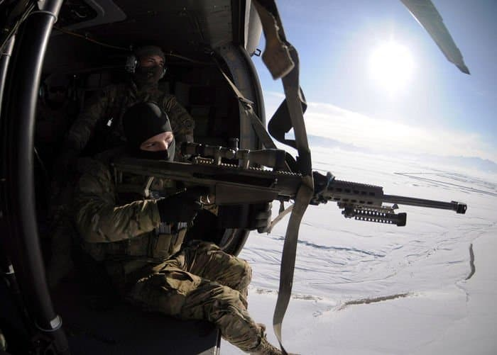 U.S. Army Cpl. William Hopkins, a spotter with 82nd Combat Aviation Brigade Pathfinders, looks through the scope of the Barrett .50 Cal. while U.S. Army Sgt. Lucas Cordes, a sniper team leader waits for the Uh60 Blackhawk to turn around.