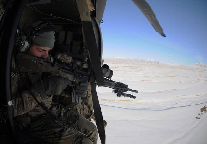 U.S. Army Sgt. Lucas Cordes, a sniper team leader, fires a customized M16 at a target while hovering in a UH 60 Blackhawk during an aerial firing platform exercise.