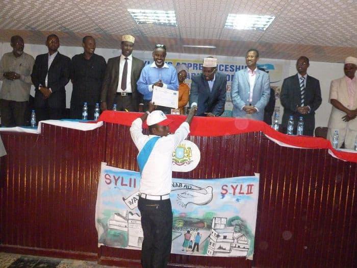 Somali President, Sheik Sharif Sheik Ahmed shakes hands with a graduating student.