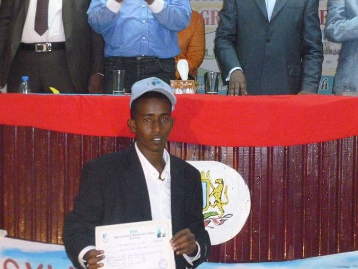 A graduate holds up his certificate.