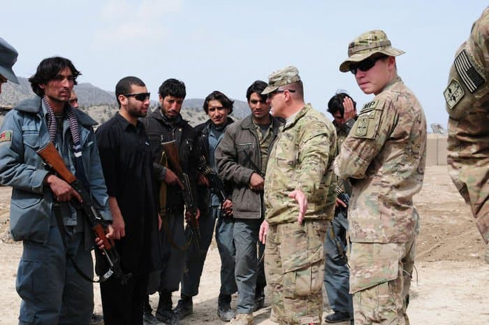 U.S. Army Sgt. 1st Class J. Scott Herring, platoon sergeant and U.S. Army Spc. Zachary Brummett, of Ooltewah, Tenn., both with the 554th Military Police Company discuss with Afghan Uniformed Police how and why they reacted in an improvised explosive device awareness class at Combat Outpost Zerok