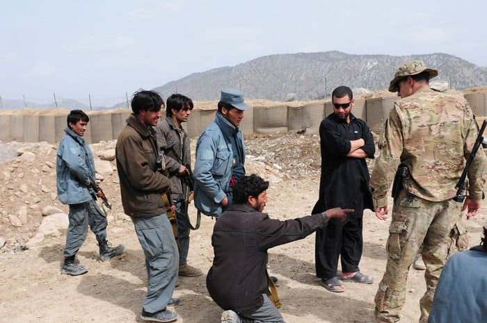 Asadullah Shabaz (wearing hat), a radio telephone operator for the Afghan Uniformed Police, leads a squad through an improvised explosive device awareness lane at Combat Outpost Zerok.