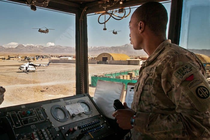 U.S. Army Spc. Quentin Bradford, from North Chicago, Ill., an air traffic control specialist for 3rd Battalion, 82nd Combat Aviation Brigade, Task Force Corsair, guides two CH 47 Chinooks as they descend onto his flight line on FOB Shank.