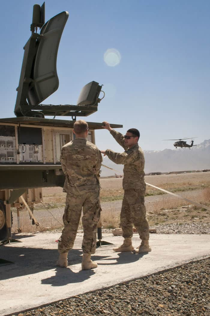 U.S. Army Specialists Luke Perkinson, from College Station, Texas, and Peter Meppen, from Nassau, N.Y., air traffic control specialists with 3rd Battalion, 82nd Combat Aviation Brigade, Task Force Corsair, check out the sensor pallet for the FOB Shank air field as a UH 60 Black Hawk executes a low approach.